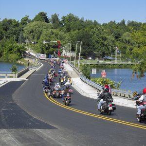 motorcycle parade across bridge over water