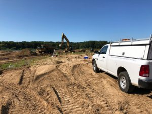 A white Prein&Newhof truck at a construction site. Prein&Newhof is one of the leading civil engineering companies in Michigan.