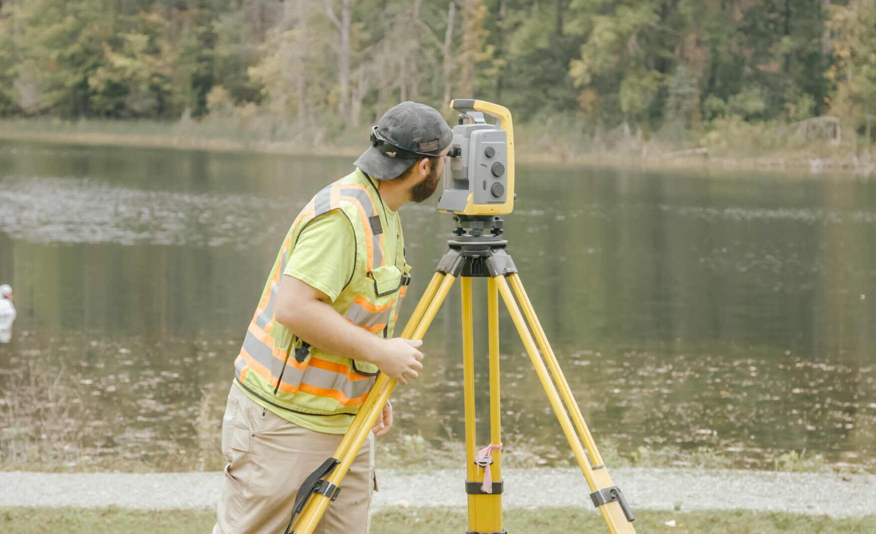 Surveyer using surveying equipent to survey a river