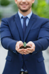 Close up of businessman holding dirt and leaf in his hands